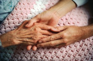 nurse holding hand of elderly person